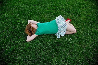 A young woman lying on grass - p3017801f by Jane