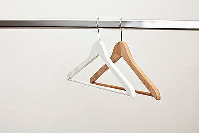 White and brown coat hanger on rail - p301m714380f by Larry Washburn