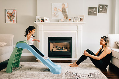 Girl sliding down living room slide, mother watching - p924m2090913 by Sara Monika