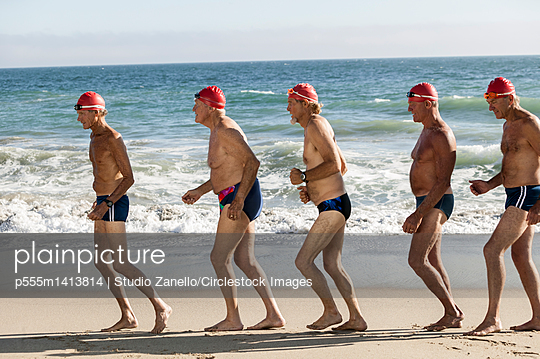 Older men on swimming team running on beach