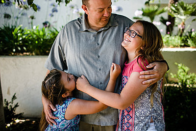 Happy daughters embracing father while standing at park - p1166m2025190 by Cavan Images