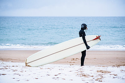 Young woman going winter surfing in snow - p1166m2177042 by Cavan Images