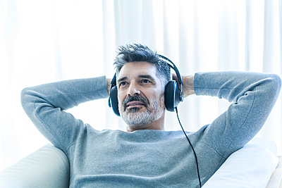 Relaxed mature man at home wearing headphones - p300m1416588 by Tom Chance