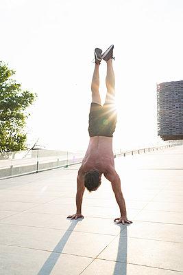 Barechested man doing a handstand at sunset - p300m2154850 by Francesco Buttitta