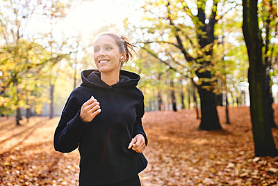 Young woman jogging in autumn forest - p300m2213942 by Bartek Szewczyk
