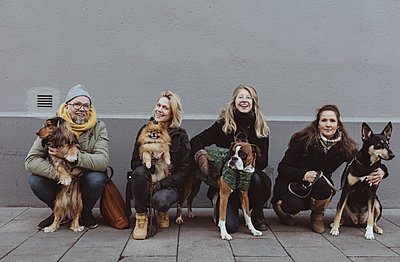 Portrait of smiling pet owners with dogs on footpath against wall in city - p426m2194774 by Maskot