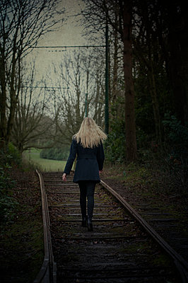 Woman walking away on tracks  - p794m899031 by Mohamad Itani