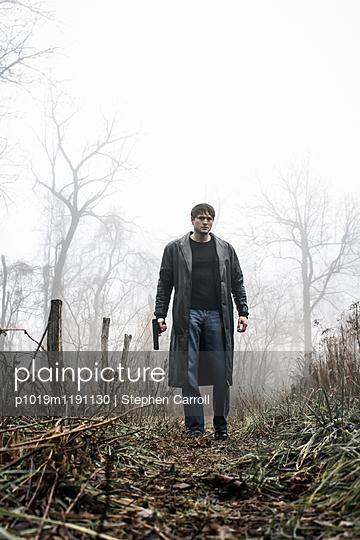 Man in Foggy Landscape with Gun - p1019m1191130 by Stephen Carroll