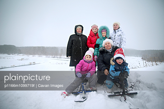 Happy family on snow covered field against sky - p1166m1099719f by Cavan Images