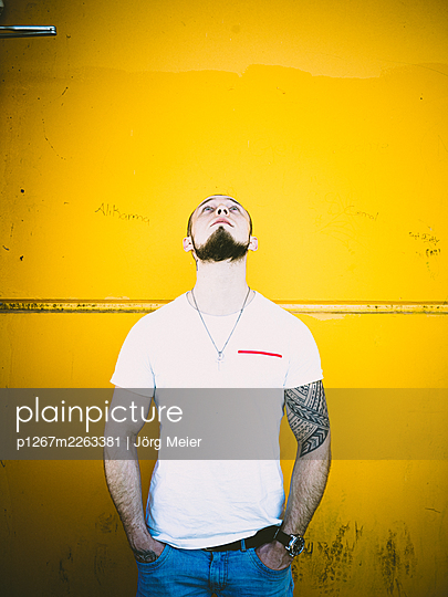 Man with tattoo and pigtail against yellow wall - p1267m2263381 by Jörg Meier