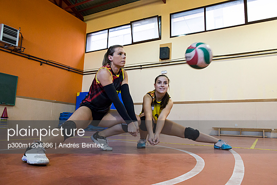 Two volleyball players digging the ball during a volleyball match