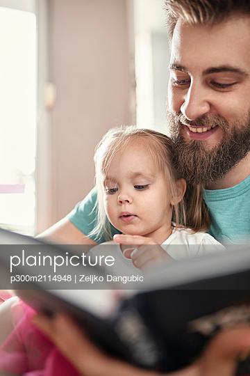 Father and daughter reading a book - p300m2114948 von Zeljko Dangubic