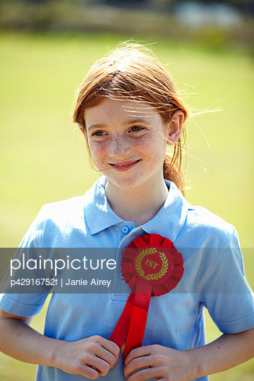 Smiling girl wearing first place ribbon - p42916752f by Janie Airey