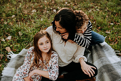 High angle view of brother embracing mother while sister sitting by her on picnic blanket at park - p1166m1555654 by Cavan Images