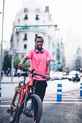 Portrait of young man with e bike in the city - p300m2121679 von Oscar Carrascosa Martinez