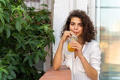 Portrait of young woman drinking glass of orange juice - p300m2131681 by VITTA GALLERY