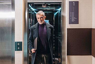 Mature businessman with laptop and luggage walking out of lift in hotel - p300m2273789 by Daniel González