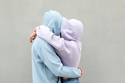 Couple in hooded shirt embracing each other by wall - p300m2277432 by Petra Stockhausen