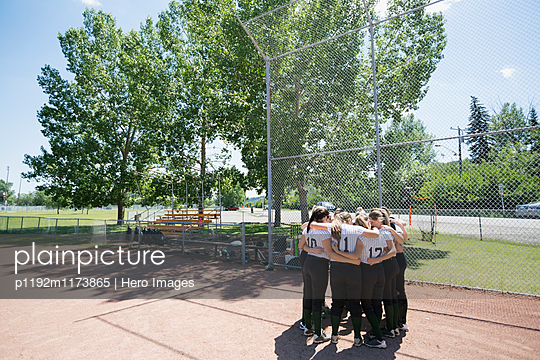 Middle school girl softball team in huddle on baseball diamond