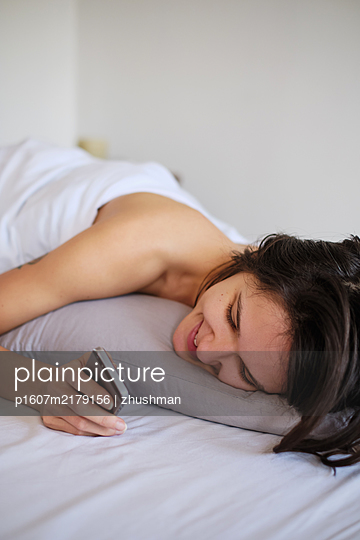 Young woman interact with her smartphone while laying in the bed - p1607m2179156 by zhushman