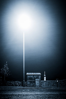 A bus stop under a street lamp on a rainy night in Consett, County Durham, UK - p1302m2142106 by Richard Nixon