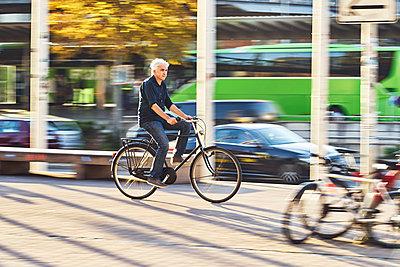 Mann auf dem Fahrrad unterwegs in der Stadt - p1312m1515405 von Axel Killian