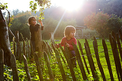 Two children playing in the garden - p1511m2223090 by artwall