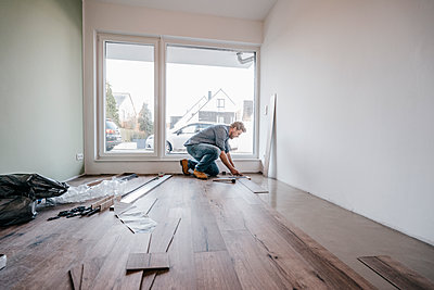 Mature man fitting flooring in new home - p300m1226546 by Joseffson