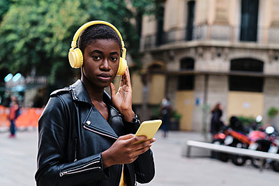 Woman listening music while standing in city - p300m2250168 by Alvaro Gonzalez