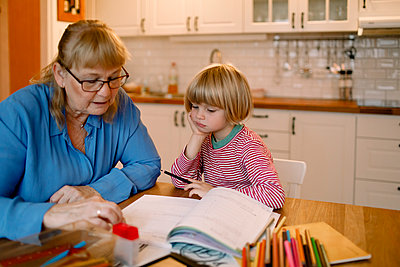 Grandmother assisting grandson in doing homework at home - p426m2195094 by Maskot