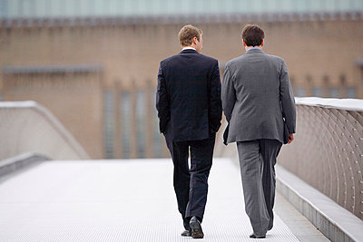 Businessmen walking on bridge together - p42915257f by Mark John