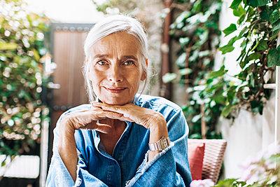 Glückliche Seniorin stützt Kinn auf ihre Hände - p608m2203547 von Jens Nieth