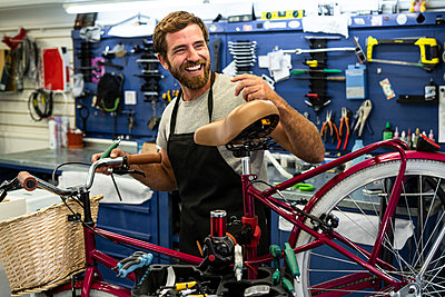 Mechanic repairing bicycle in workshop - p623m2214734 by Frederic Cirou