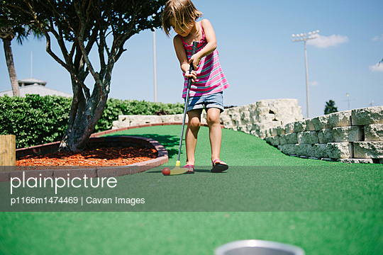 Girl playing miniature golf during sunny day
