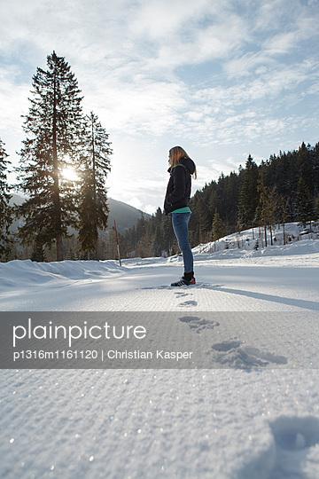 Junge Frau steht im Schnee, Spitzingsee, Oberbayern, Bayern, Deutschland - p1316m1161120 von Christian Kasper