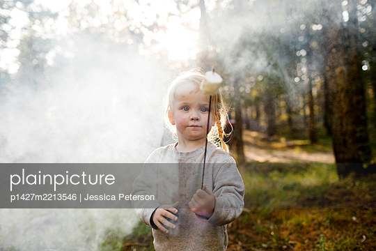 Portrait of girl (2-3) holding marshmallow near campfire in forest, Wasatch Cache National Forest - p1427m2213546 by Jessica Peterson