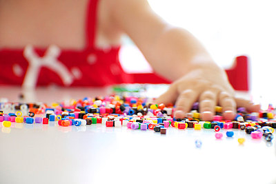 Girl Playing With Ironing Beads - p1026m762553f by Alexandra Dost