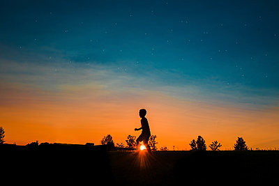 Silhouette boy walking on field against sky during sunset - p1166m1568698 by Cavan Images