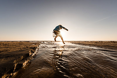 Toddler boy jumping over water on a sunny morning at a beach - p1166m2108119 by Cavan Images