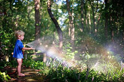 Junge spielt mit Gartenschlauch - p1169m993957 von Tytia Habing
