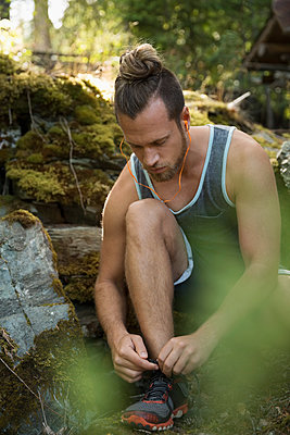Runner tying shoelace in woods - p1192m1078309f by Hero Images