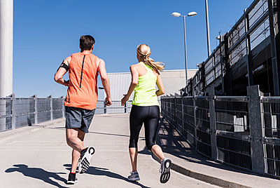 Fit couple jogging in the city - p300m1588004 von Uwe Umstätter