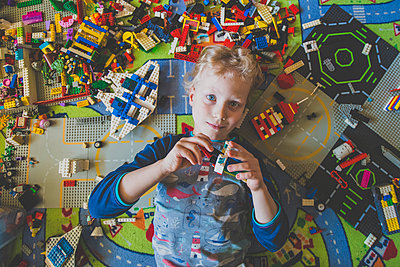 High angle portrait of boy playing with toy blocks at home - p300m2188884 by Irina Heß