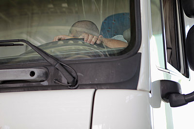 Low angle view of driver sleeping in truck seen through windshield - p301m1130843f by Marc Volk
