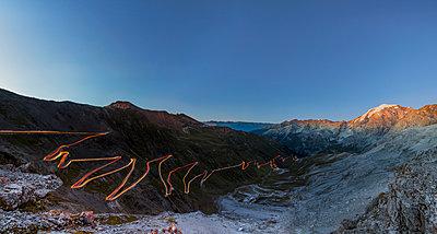 Panorama of lights of car trace at dusk, Stelvio Pass, Valtellina, Lombardy, Trentino Alto Adige, Italy, Europe - p871m1478708 by Roberto Moiola