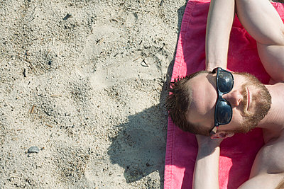 Overhead view of mid adult man in sunglasses sunbathing on sand - p924m947262f by Ashley Corbin-Teich