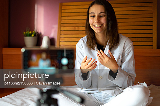 Female doctor recording a video with her mobile. Online doctor. - p1166m2190586 by Cavan Images