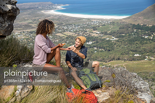 Young hiking couple takes a break in the mountains - p1355m1574190 by Tomasrodriguez