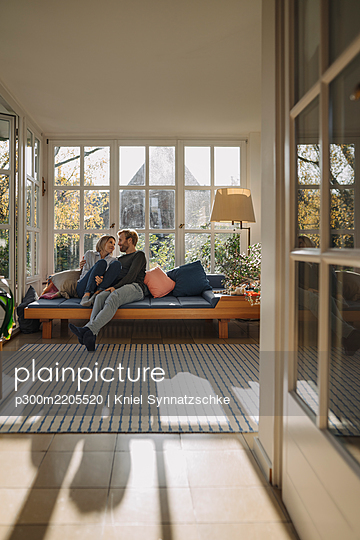 Affectionate couple relaxing in sunroom at home - p300m2205520 by Kniel Synnatzschke