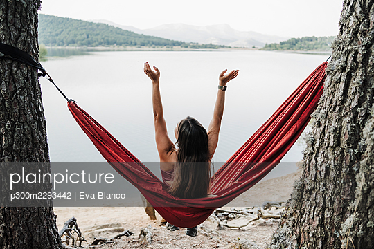 Woman with arms raised sitting on hammock in forest - p300m2293442 by Eva Blanco